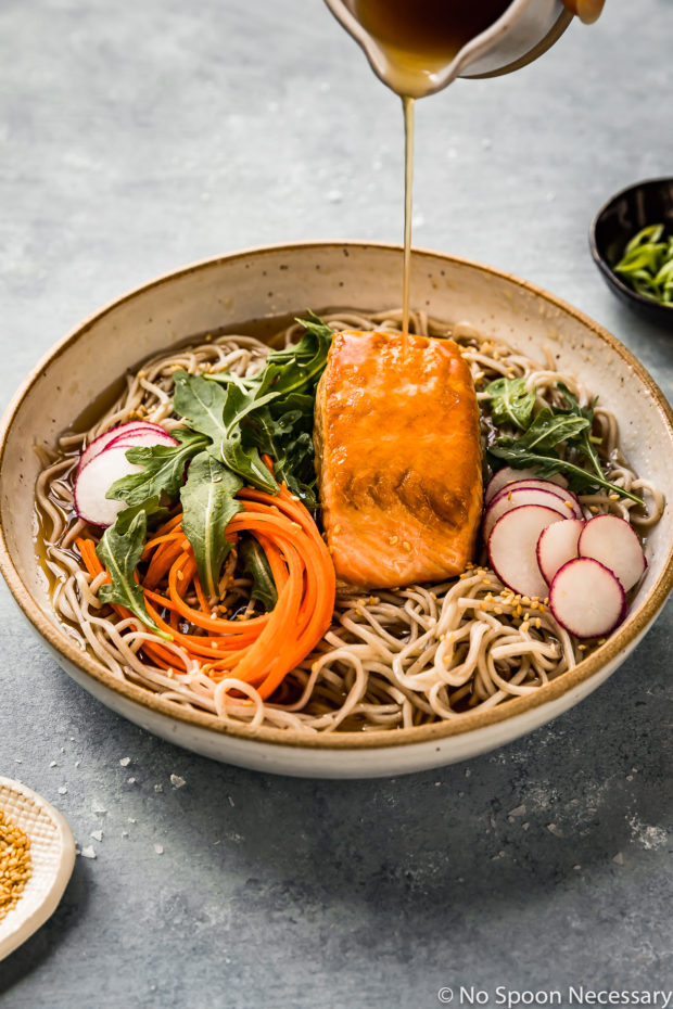 Angled shot of Green Tea Poached Salmon Soba Noodles with arugula, sliced radishes and julienned carrots in a neutral colored bowl with hot tea broth being poured over the salmon; and a ramekin of sesame seeds and sliced scallions arranged around the bowl (photo of step 7 of the recipe).