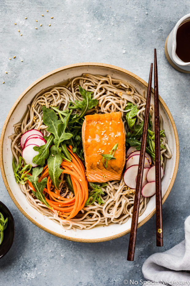 Overhead shot of Green Tea Poached Salmon Soba Noodles with arugula, sliced radishes and julienned carrots in a neutral colored bowl with chopsticks resting on the edge; and a ramekin of sliced scallions and a jar of tea broth arranged around the bowl.