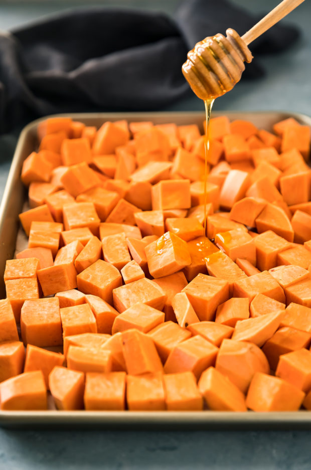 45 degree angle photo of a wooden honey stick drizzling honey over a sheet pan full of peeled and diced sweet potatoes with a dark blue linen blurred in the background - photo of the first step of the recipe.