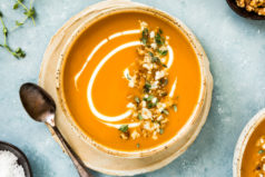 Overhead photo of Creamy Sweet Potato Soup garnished with walnuts, thyme, gorgonzola and swirls of cream in a neutral colored bowl on a plate with sprigs of fresh thyme, a spoon, additional bowl of soup and small brown ramekins of walnuts and salt surrounding the bowl.