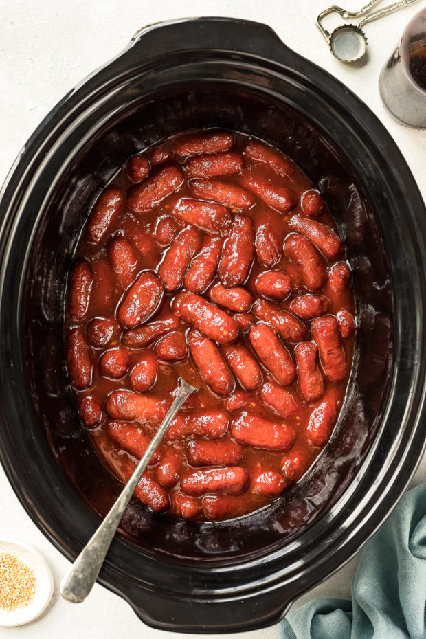 Overhead shot of cooked honey sriracha little smokies in black slow cooker with a spoon inserted into the cooker - photo of step 3 of the Slow Cooker Honey Sriracha Little Smokies recipe.