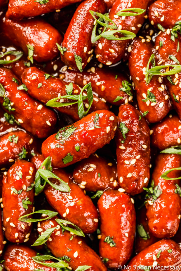 Overhead, up close shot of Slow Cooker Honey Sriracha Little Smokies garnished with sesame seeds, sliced scallions and minced cilantro.