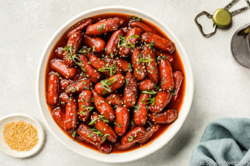 Overhead shot of a white bowl filled with Slow Cooker Honey Sriracha Little Smokies and garnished with sesame seeds and sliced scallions; with a ramekin of sesame seeds, blue linen, a beer bottle, cap and bootle opener arranged around the bowl.