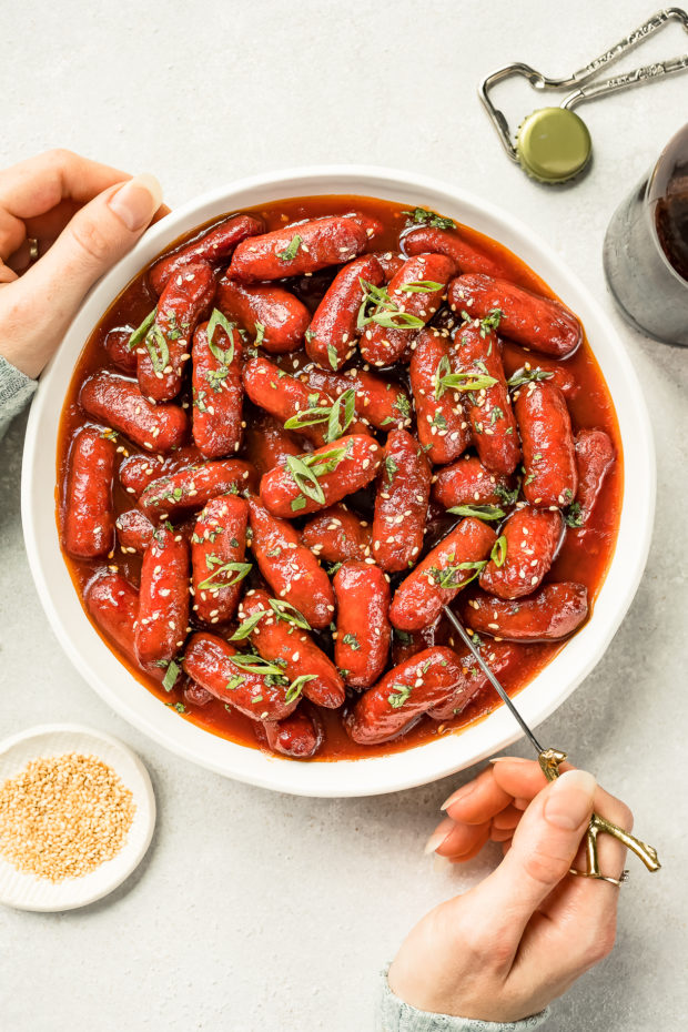 Overhead shot of two hands holding a white bowl filled with Slow Cooker Honey Sriracha Little Smokies and garnished with sesame seeds and sliced scallions; with a ramekin of sesame seeds, a beer bottle, cap and bootle opener arranged around the bowl.