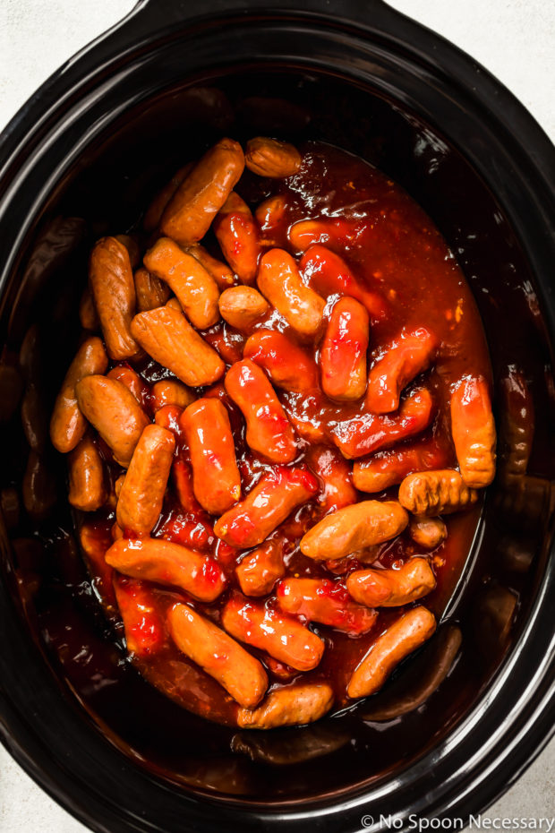 Overhead shot of little smokies covered with honey sriracha sauce in a black slow cooker - photo of the second part of step 2 of the Slow Cooker Honey Sriracha Little Smokies recipe.