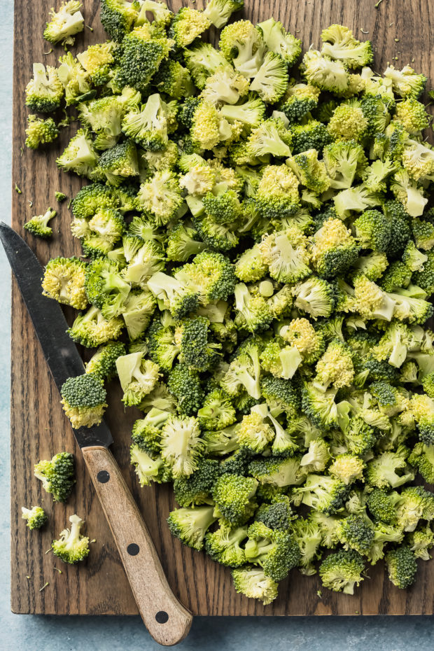 Overhead photo of a head of fresh broccoli cut into bite-size florets on a large wood cutting board with a knife next to the florets.