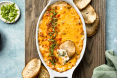 Overhead photo of Broccoli Dip in a white oval baking dish with a slice of toasted baguette inserted into the dip and slices of baguette, a green linen, and ramekins of sliced scallions and salt surrounding the baking dish.
