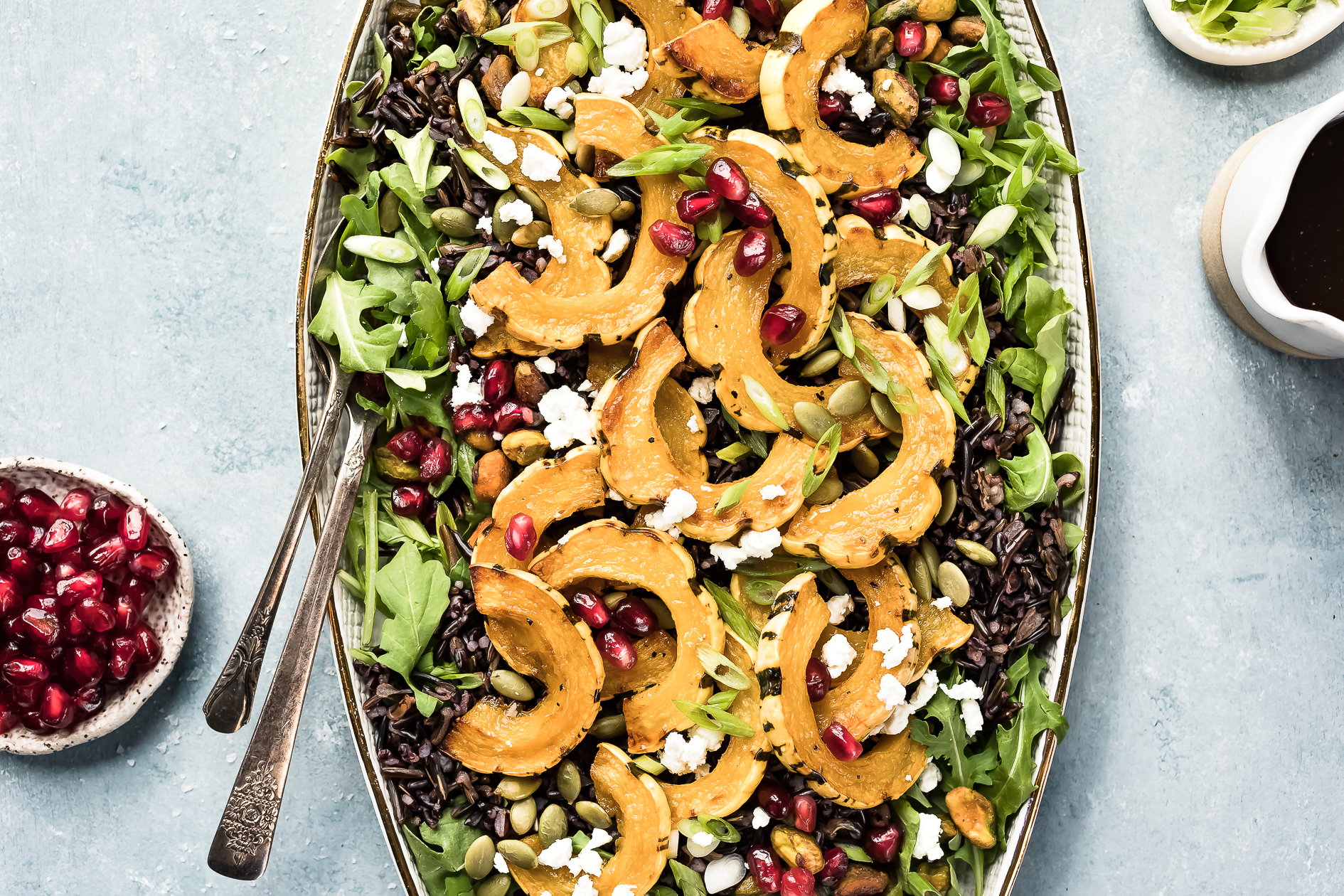 Overhead photo of Wild Rice Salad featuring roasted delicata squash, pomegranate arils and sliced scallions on a white platter with serving spoons inserted into the salad; and ramekins of pomegranate arils, sliced scallions and a small container of honey balsamic vinaigrette arranged around the salad.