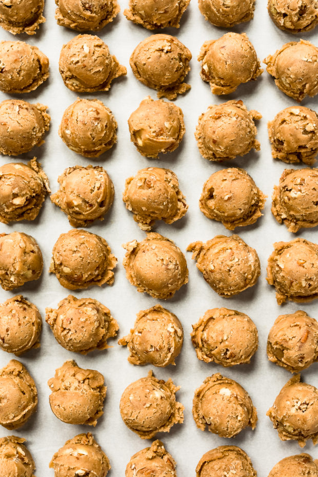 Overhead photo of Pecan Cookie dough scooped into individual balls on a piece of parchment paper - photo of the first part of step 6 of the recipe.