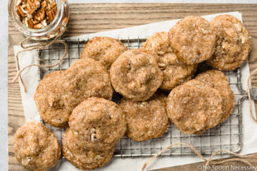 Overhead, landscape shot of Maple Brown Sugar Pecan Cookies on a small wire cooling rack with a small jar of chopped pecans and a glass of milk arranged around the cookies.