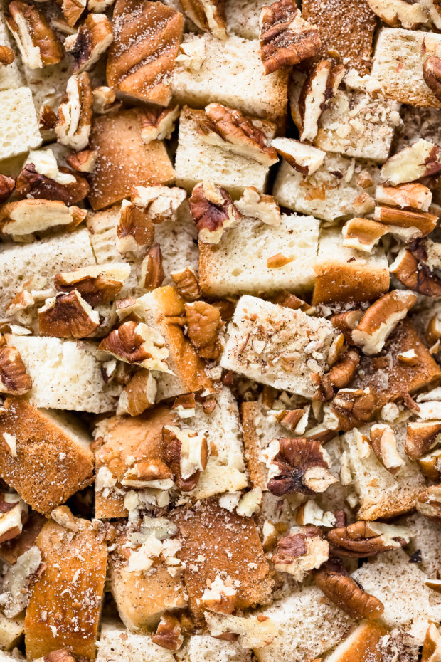 Overhead, up close shot of cubes of brioche bread sprinkled with cinnamon and chopped pecans - photo of the second part of step 2 of the Cinnamon French Toast Casserole recipe.