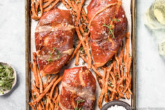 Overhead shot of Brown Sugar Prosciutto Wrapped Chicken & Sweet Potato Fries on a sheet pan with a ramekin of flaky salt; with a light green linen, ramekin of microgreens and two glasses of white wine arranged around the pan.