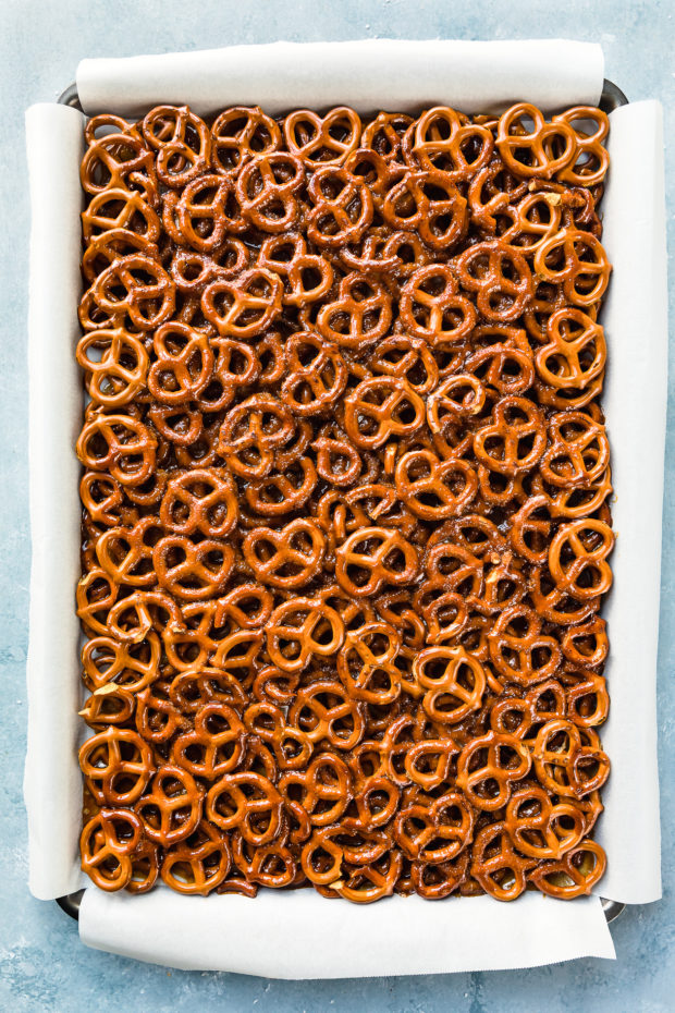 Overhead photo of a rimmed cookie sheet lined with parchment paper and filled with a layer of pretzels covered with toffee - photo of step 5 of the recipe.