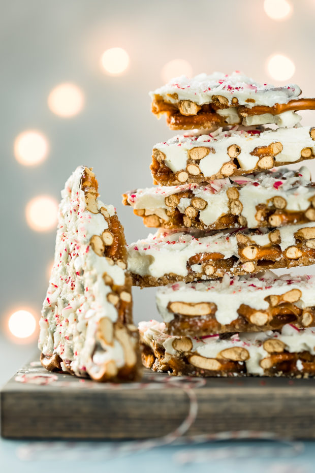 Straight on photo of pieces of Chocolate Peppermint Bark stacked on top of each other on a gray wood board with one piece off to the side.