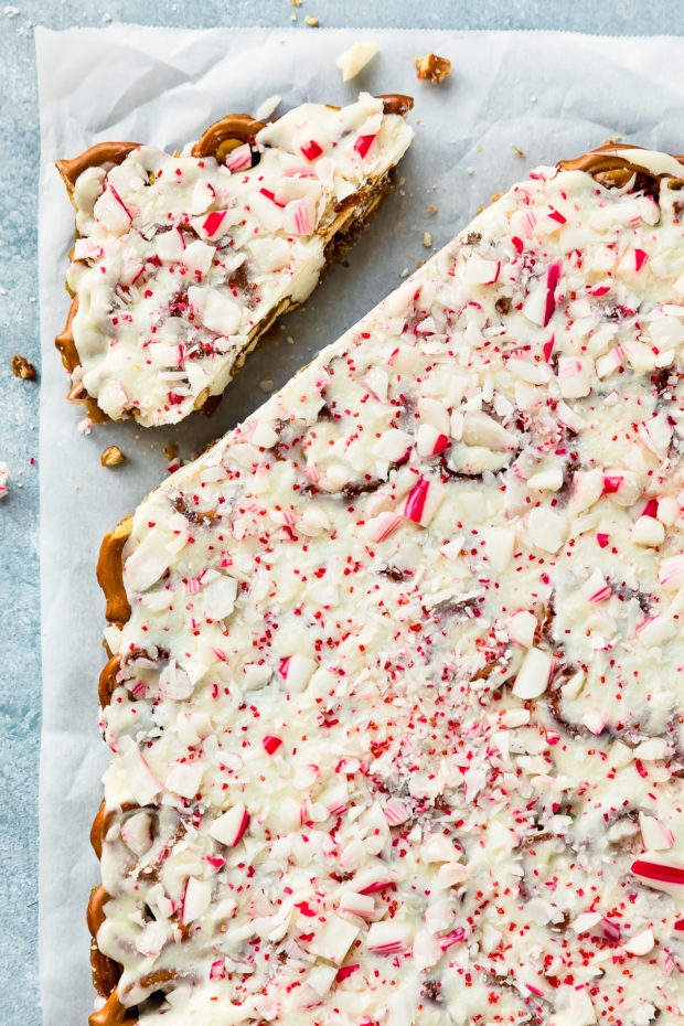 Overhead photo of Pretzels Bark with peppermint on a piece of parchment paper with a piece of bark cut off and separated.