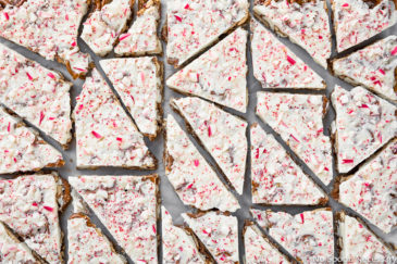 Overhead photo of Peppermint White Chocolate Covered Pretzels Bark cut into pieces on a piece of parchment paper.