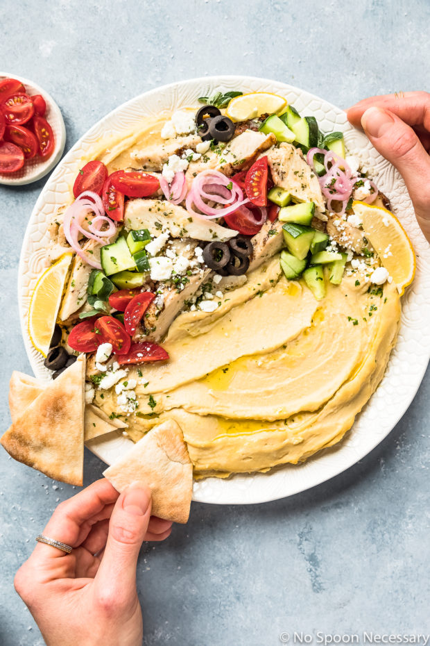 Overhead photo of Greek Chicken Loaded Hummus Bowl on a large white platter with a hand dipping a pita triangle into the hummus and a ramekin of halved cherry tomatoes next to the platter.