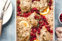 Overhead, landscape photo of Baked Orange Cranberry Chicken & Rice in a white casserole dish garnished with orange slices and fresh thyme with a ramekin of cranberries, neutral linen, stack of plates, knife and carving fork arranged around the dish.