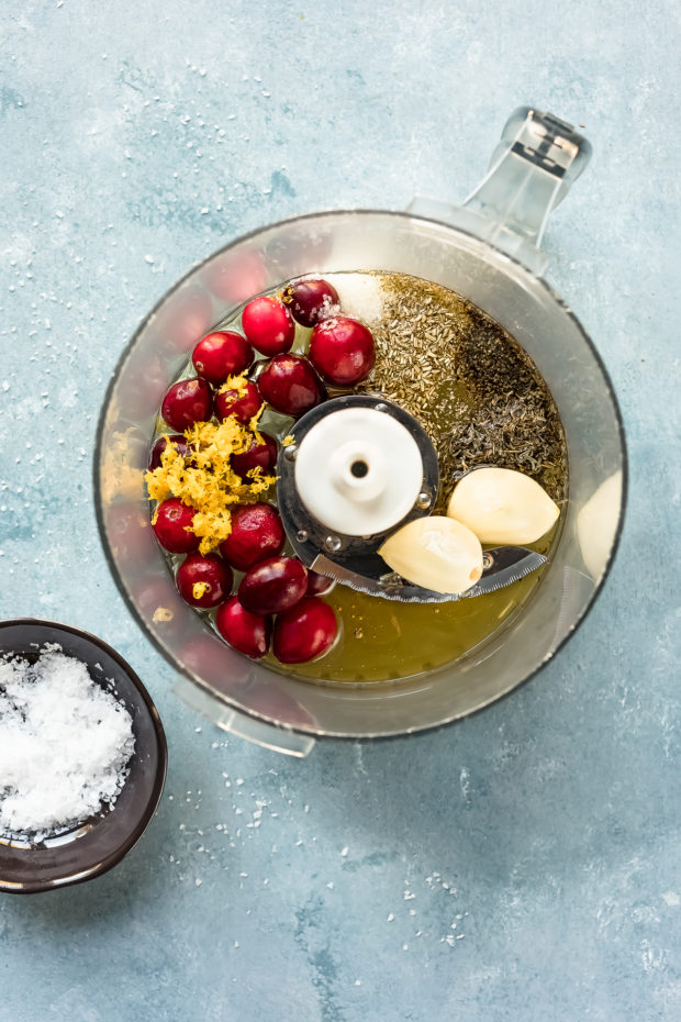 Overhead photo of a small food processor bowl filled with the ingredients to make orange cranberry marinade - step 1 of the Baked Orange Cranberry Chicken & Rice recipe.