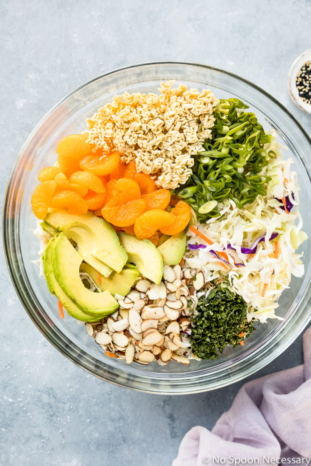 Overhead photo of a large glass bowl neatly filled with ramen, mandarin orange segments, sliced scallions, avocado, sliced almonds, chopped cilantro, coleslaw and sliced scallions before tossing together - photo of step 3 of the Orange Shrimp Ramen Noodle Salad recipe.