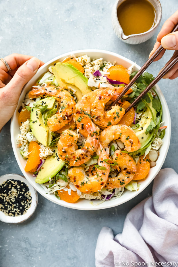 Overhead photo of Healthy Orange Shrimp Ramen Noodle Salad with coleslaw and sliced avocado in a white bowl with a hand holding chopsticks inserted into the bowl and a ramekin of sesame seeds, a purple linen and a small jar of Asian dressing surrounding the bowl.