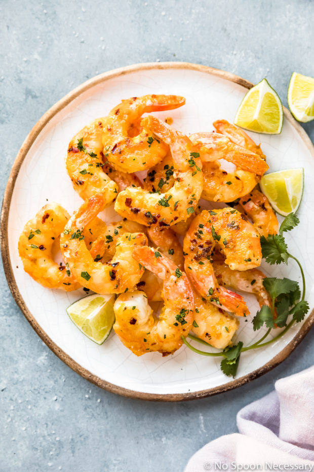 Overhead photo of healthy orange stir-fried shrimp on a white plate with slices of lime and fresh cilantro - photo of step 4 of the Orange Shrimp Ramen Noodle Salad recipe.