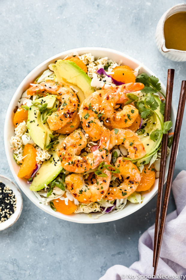 Overhead photo of Healthy Orange Shrimp Ramen Noodle Salad with coleslaw and sliced avocado in a white bowl with a pair of chopsticks resting on the side of the bowl and a ramekin of sesame seeds, a purple linen and a small jar of Asian dressing surrounding the bowl.