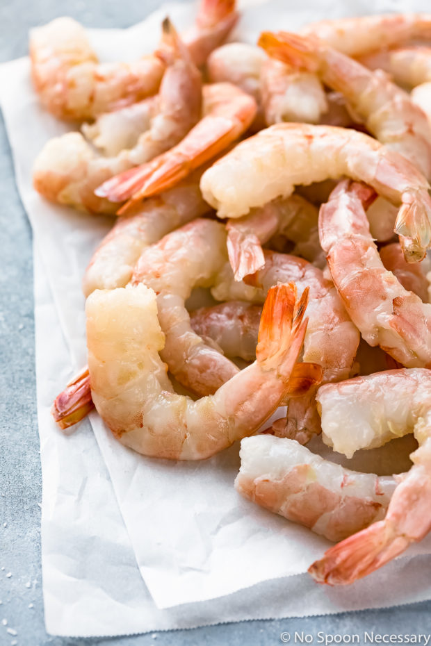 Angled photo of peeled and deveined jumbo shrimp on a piece of white parchment paper - prep photo for Orange Shrimp Ramen Noodle Salad recipe.