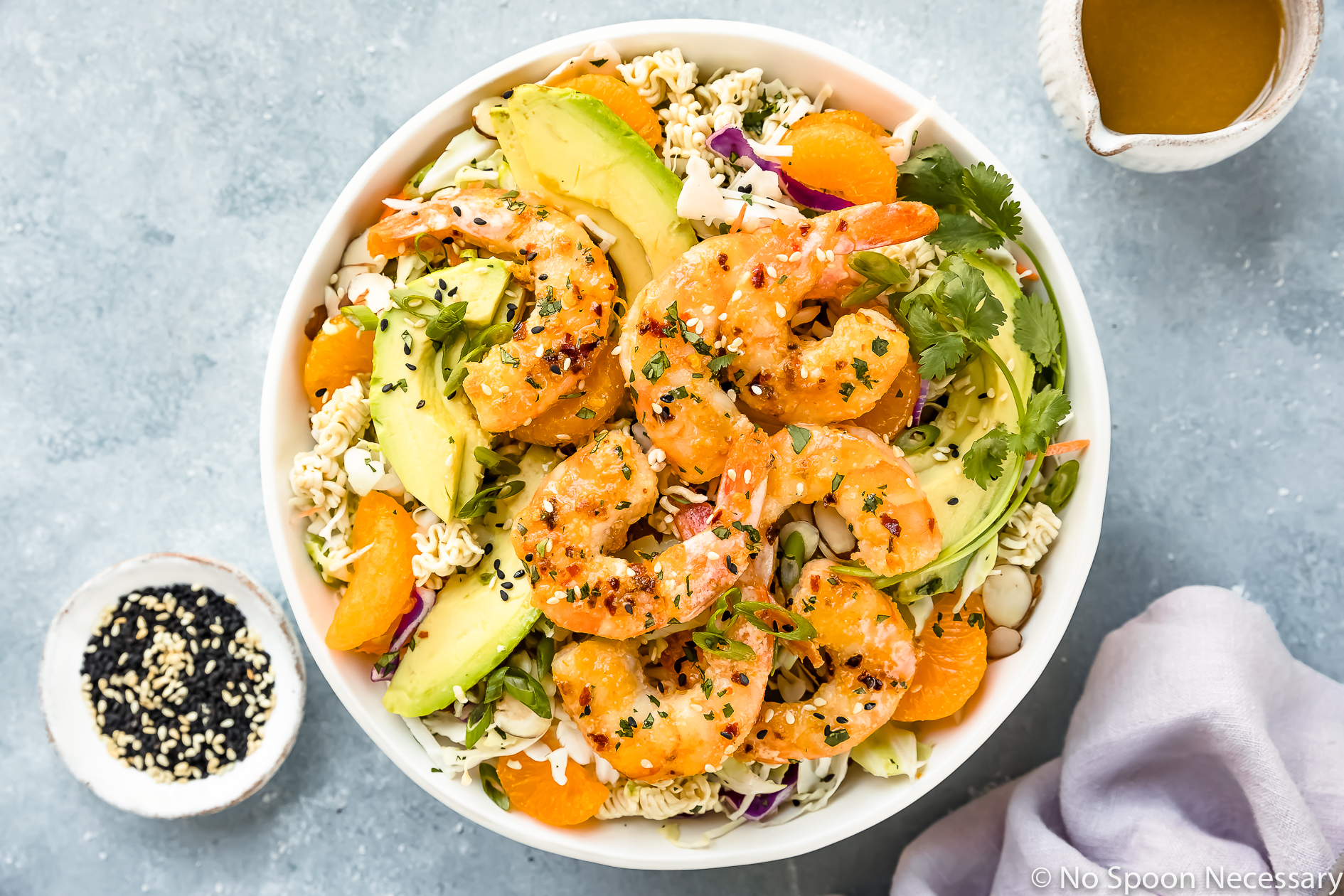 Overhead photo of Healthy Orange Shrimp Ramen Noodle Salad with coleslaw and sliced avocado in a white bowl with a ramekin of sesame seeds, a purple linen and a small jar of Asian dressing surrounding the bowl.