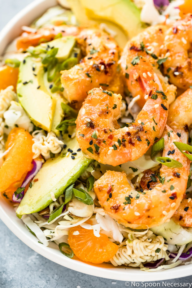 Angled, up close photo of Healthy Orange Shrimp Ramen Noodle Salad with coleslaw and sliced avocado in a white bowl.
