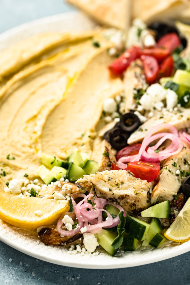 Angled, close-up photo of a Mediterranean Hummus Bowl topped with chicken on a large white platter.