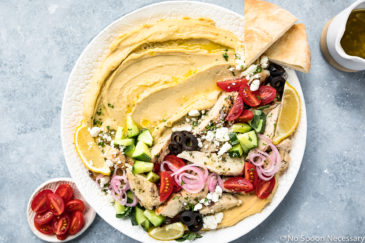 Overhead photo of Greek Chicken Loaded Hummus Bowl on a large white platter with pita triangles and a ramekin of halved cherry tomatoes and a jar of Greek vinaigrette arranged around the platter.