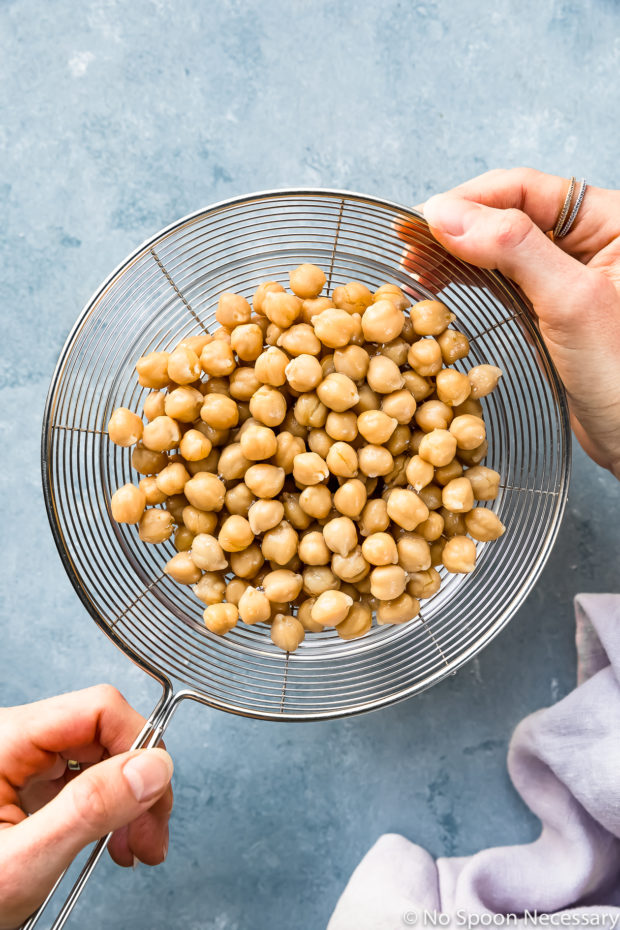 Overhead photo of cooked chickpeas draining in a wire sieve over a glass bowl with two hands holding the sieve - prep photo for Crispy Honey Roasted Chickpeas recipe.
