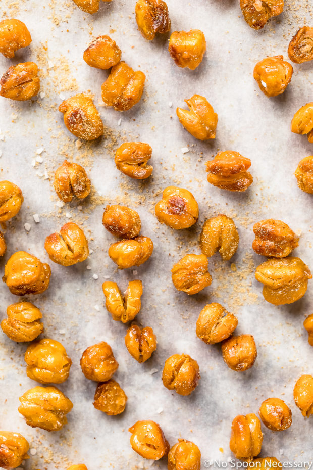 Overhead, up-close photo of Crispy Honey Roasted Chickpeas dusted with ground ginger and sprinkled with flaky sea salt on a piece of parchment paper.