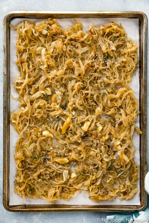 Overhead photo of Oven Caramelized Onions on a parchment paper lined sheet pan with a pale blue linen tucked in the corner of the shot.