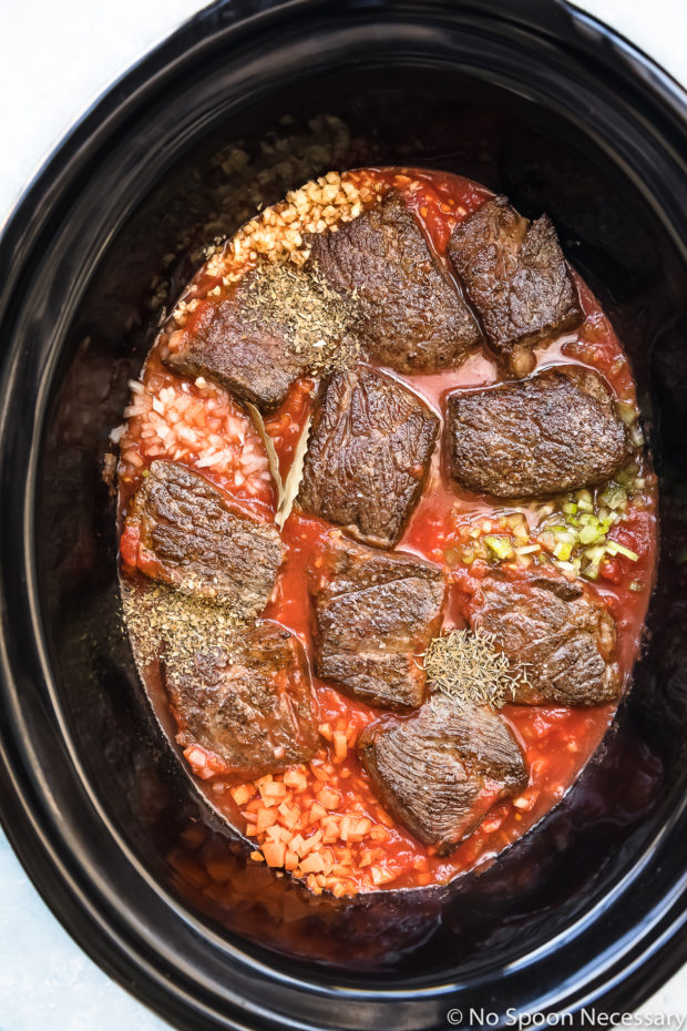Overhead photo of browned short ribs, vegetables, seasonings and crushed tomatoes in the pot of a slow cooker - photo of the first part of step 3 of the Slow Cooker Short Rib Ragu Bolognese recipe.