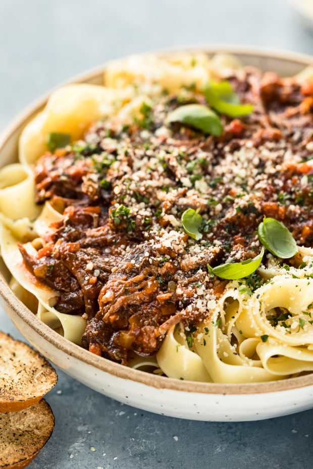 Angled photo of Slow Cooker Short Rib Ragu Bolognese over papparelle pasta in a neutral colored serving bowl with slices of toasted baguette in front of the bowl and a ramekin of grated parmesan cheese blurred behind the bowl.