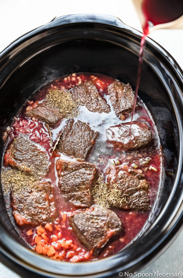 Overhead photo of red wine being poured over browned short ribs, vegetables, seasonings and crushed tomatoes in the pot of a slow cooker - photo of the second part of step 3 of the Slow Cooker Short Rib Ragu Bolognese recipe.
