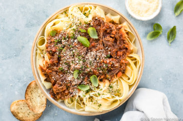 Overhead photo of Slow Cooker Short Rib Ragu Bolognese over papparelle pasta in a neutral colored serving bowl with slices of toasted baguette, fresh basil leaves, a ramekin of grated parmesan cheese and a pale blue linen arranged around the bowl.