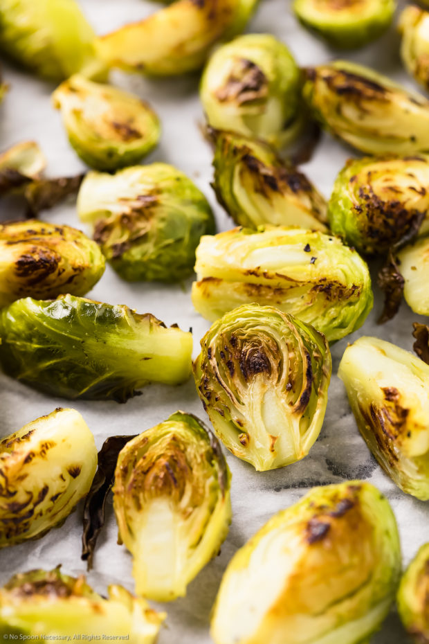 Angled close-up photo of crispy roasted brussels sprouts on a parchment paper lined sheet pan - step 3 of the recipe.