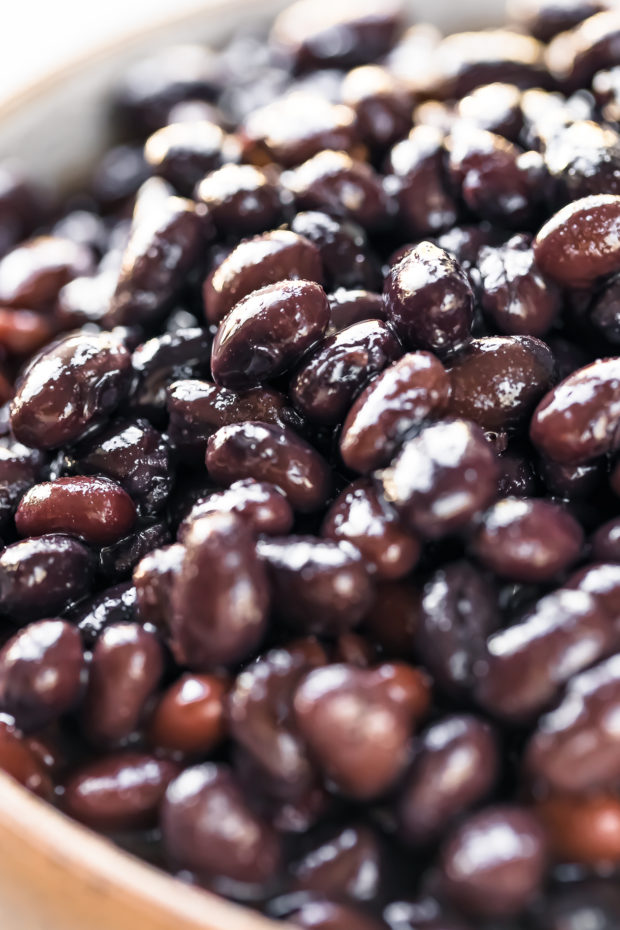 Angled, up-close photo of rinsed and drained canned black beans in a small bowl - photo of the main ingredient in Cuban Black Beans Recipe.