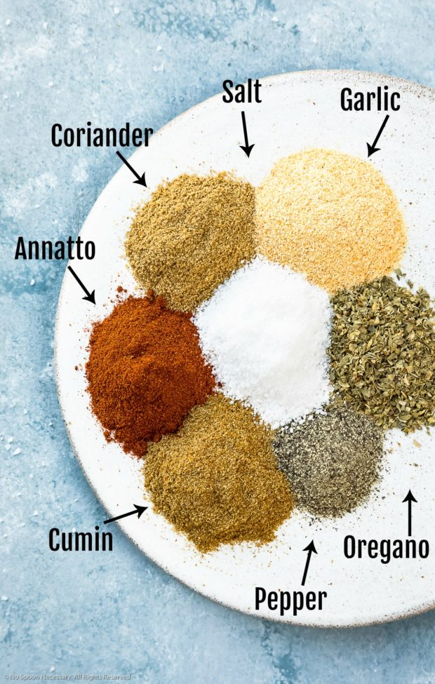Overhead photo of all the ingredients needed to make Homemade Sazon Seasoning Mix neatly organized into individual piles on a white plate with the name of each ingredient written out next to it - photo of step 1 of the Homemade Sazon Seasoning Mix recipe.