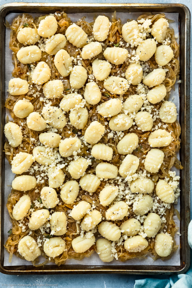 Overhead photo of a caramelized onions topped with unbaked gnocchi and grated parmesan on a sheet pan - photo of the second part of step 5 of French Onion Baked Gnocchi Recipe.