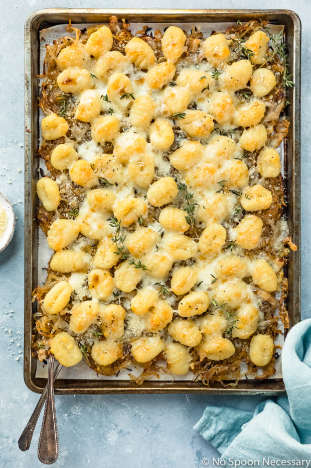 Overhead photo of French Onion Baked Gnocchi drizzled with balsamic reduction on a sheet pan with forks inserted under the gnocchi and a ramekin of grated parmesan next to the pan.