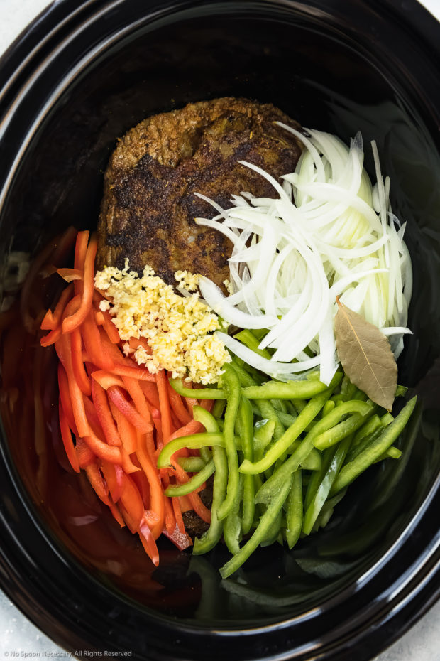 Overhead photo of a black slow cooker bowl filled with browned flank steak, sliced onions, sliced bell peppers, minced garlic and a bay leaf - photo of the first part of step 3 of the Slow Cooker Ropa Vieja recipe.