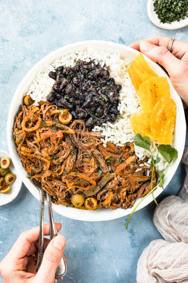 Overhead photo of Slow Cooker Ropa Vieja, white rice, black beans and plantain chips in a white bowl with a hand holding the side of the bowl and another hand inserting serving spoons into the ropa vieja and ramekins of halved olives and chopped cilantro arranged around the bowl.