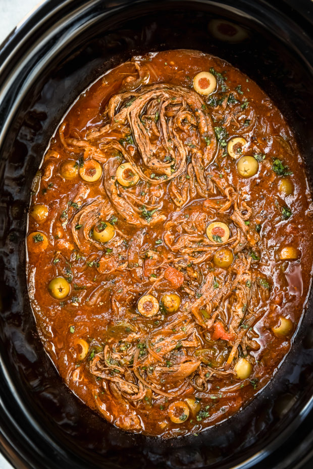 Overhead photo of Ropa Vieja garnished with fresh cilantro in a black slow cooker - photo of step 6 of the Slow Cooker Ropa Vieja recipe.