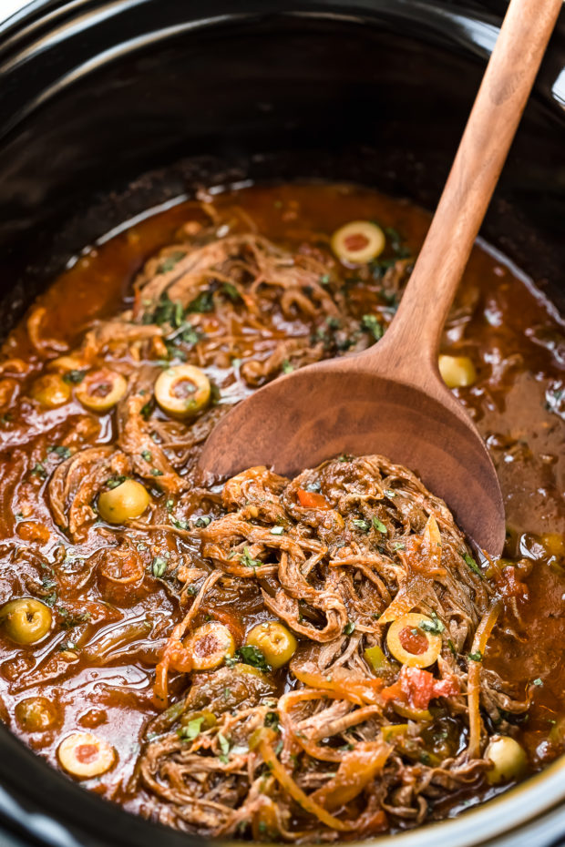 Angled photo of ropa vieja in a black slow cooker with a large wooden spoon scooping up the shredded beef.