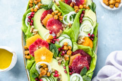 Overhead photo of Winter Citrus Salad with avocado, cucumbers and mint on a large white platter with a pale purple linen and ramekins of honey citrus vinaigrette and crispy chickpeas surrounding the platter.