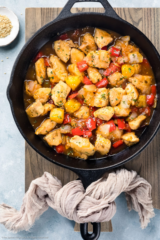 Overhead photo of apricot chicken stir-fried with onions, peppers and pineapples in a cast iron skillet - photo of step 5 of the apricot chicken recipe.